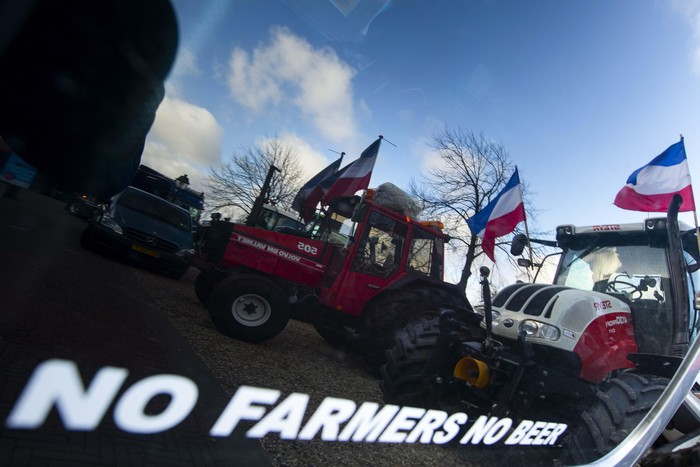 Police, front, and army trucks, rear, block the roads leading to parliament during a farmers demonstration in The Hague, Netherlands, Wednesday, Feb. 19, 2020. Dutch farmers, some driving tractors, poured into The Hague on Wednesday to protest government moves to rein in carbon and nitrogen emissions to better fight climate change. (AP Photo/Peter Dejong)