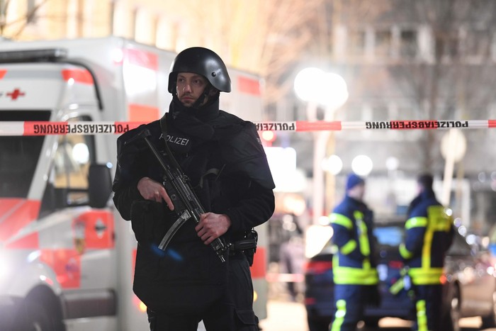Police handcuff a man near the scene of a shooting in Hanau, Germany early Thursday, Feb. 20, 2020. German police say several people were shot to death in the city of Hanau on Wednesday evening. (AP Photo/Michael Probst)
