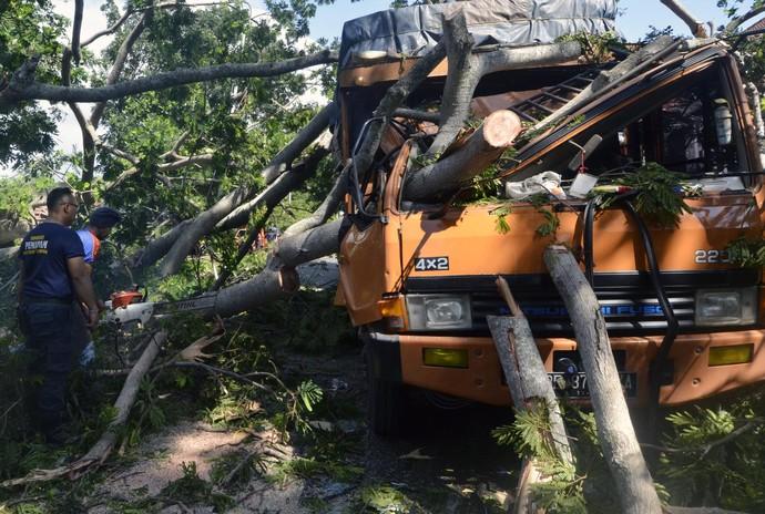 Angin kencang yang melanda kawasan Lampung membuat pohon tumbang. Truk hingga motor pun rusak akibat tertimpa pohon tumbang tersebut.