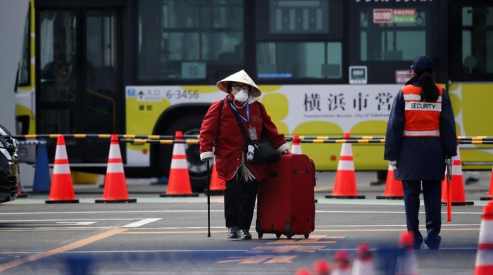 An unidentified passenger walks down after she disembarked from the quarantined Diamond Princess cruise ship Wednesday, Feb. 19, 2020, in Yokohama, near Tokyo. Passengers tested negative for COVID-19 started disembarking Wednesday. (AP Photo/Jae C. Hong)