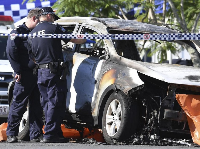 In this Wednesday, Feb. 19, 2020, photo, police attend the scene of a car fire in Brisbane, Australia. Hannah Baxter, 31, and her children Aaliyah, 6, Lainah, 4, and Trey, 3, died after their car was set alight on a street in suburban Brisbane on Wednesday morning. (Dan Peled/AAP Image via AP)