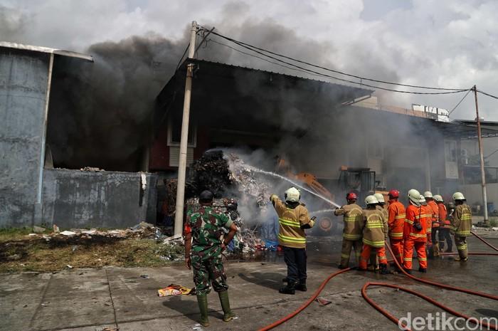 Kebakaran terjadi di kawasan Pergudangan Sentral Cakung, Cilincing, Jakut. Petugas damkar bahu membahu memadamkan api di area tersebut.