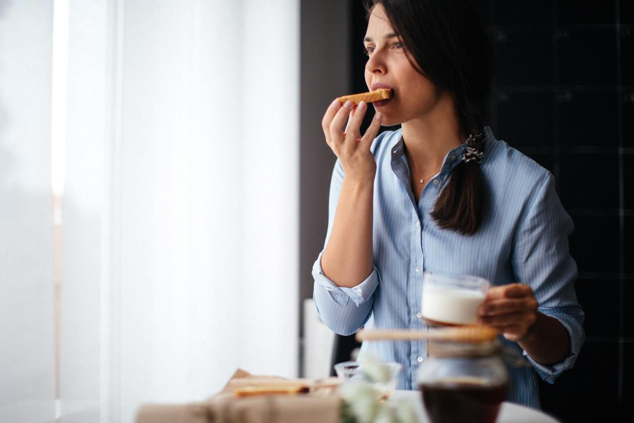 Woman eating honey on toasted bread