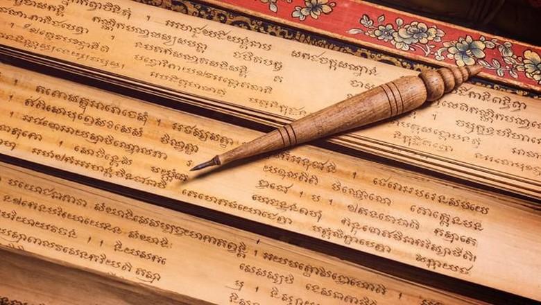 Bangkok, Thailand - November 8, 2018 : pen for writing text on Bai Lan background, Bai Lan or ancient palm leaf manuscripts content about buddhist scriptures, Pali language Khmer