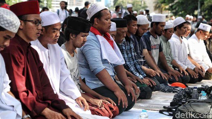 Massa Aksi 212 melaksanakan salat asar berjemaah di Jalan Medan Merdeka Barat, Jakarta, Jumat (21/2/2020). Salat berjemaah dilakukan di sela-sela aksi.