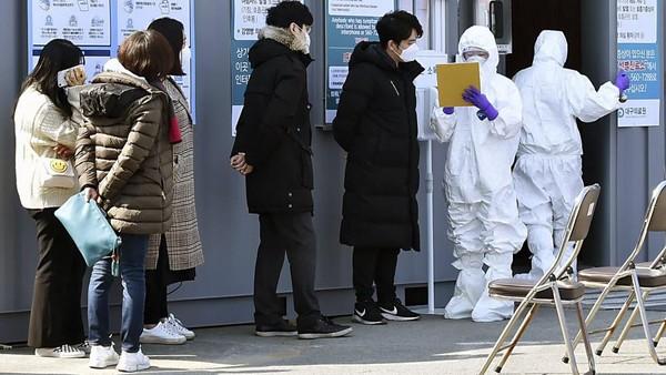 Sejumlah warga lokal yang tengah mengantre untuk dicek oleh petugas pasca merebaknya virus Corona di Daegu (Lee Moo-ryul/Newsis via AP)