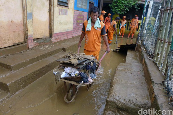 Banjir di Keluarahan Rawajati, Jakarta Selatan, telah surut. Petugas pun bahu membahu membersihkan lumpur sisa banjir.