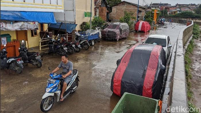 Warga memarkir kendaraan roda 4 di jalan Inspeksi Kali Ciliwung, Jakarta, Jumat (21/2/2020). Jalan tersebut merupakan hasil normalisasi pelebaran sungai Ciliwung di kawasan Kampung Pulo (sisi timur) dan Bukit Duri (sisi barat) beberapa waktu lalu. Namun, arus lalu-lintas yang tidak ramai membuat warga menjadikan satu lajur jalan sebagai lahan parkir tetap layaknya garasi mobil di rumah. Beberapa menggunakan penutup badan mobil untuk menghindari sinar matahari dan hujan. Rumah di sisi jalan hanya gang yang tidak terdapat akses untuk mobil.