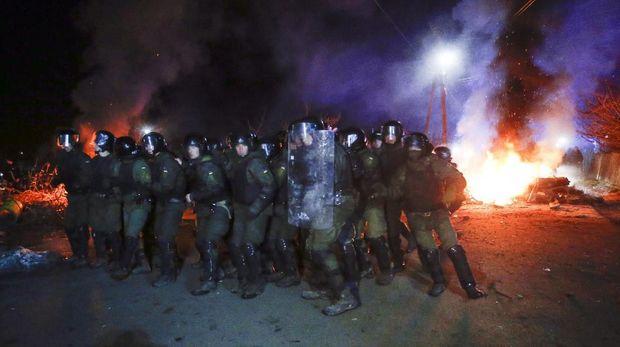 Bentrokan terjadi saat polisi hendak membuka jalan yang diblokir oleh demonstran yang menolak warga Ukraina yang dievakuasi dari Wuhan karena virus corona
