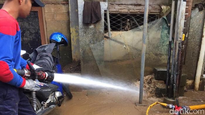 Petugas dan warga membersihkan lumpur sisa banjir di Rawajati, Pancoran, Jakarta Selatan