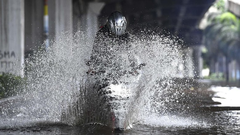 Pengendara sepeda motor mencoba melintasi banjir di Jalan Yos Sudarso, Kelapa Gading, Jakarta Utara, Minggu (23/2/2020). Hujan deras sejak Minggu 23 Februari dini hari membuat sejumlah daerah di Ibu Kota tergenang banjir. ANTARA FOTO/Sigid Kurniawan/wsj.