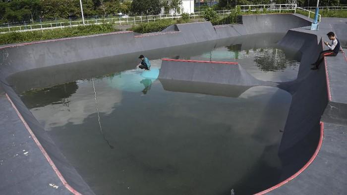 Sejumlah anak bermain di arena roller sport yang terendam air di Jakabaring Sport City (JSC), Palembang, Sumatera Selatan, Minggu (23/2/2020). Arena roller sport yang merupakan tempat pelaksanaan cabang olahraga skateboard Asian Games 2018 yang lalu tersebut terbengkalai. ANTARA FOTO/Nova Wahyudi/wsj.