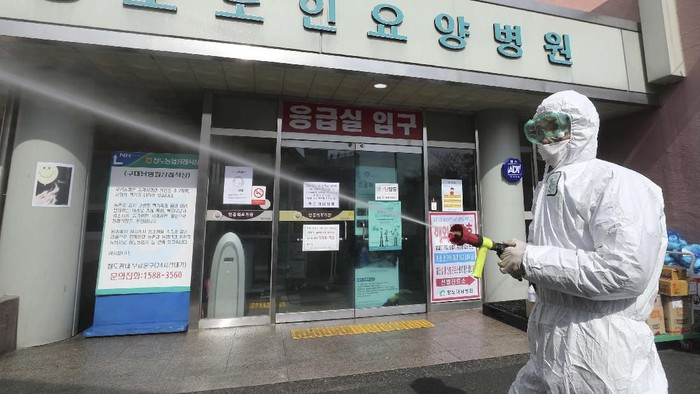A member of the medical team takes a rest outside a hospital in Daegu, South Korea, Sunday, Feb. 23, 2020. South Koreas president has put his country on its highest alert for infectious diseases, saying Sunday that officials should take unprecedented, powerful steps to fight a viral outbreak. (Im Hwa-young/Yonhap via AP)