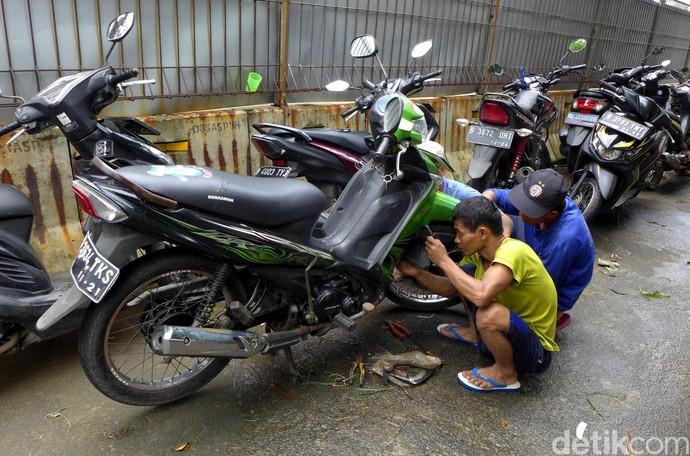Banjir turut merendam sejumlah kendaraan milik warga di kawasan Rawa Terate, Jakarta. Warga pun saling bantu memperbaiki motor-motor terdampak banjir tersebut.