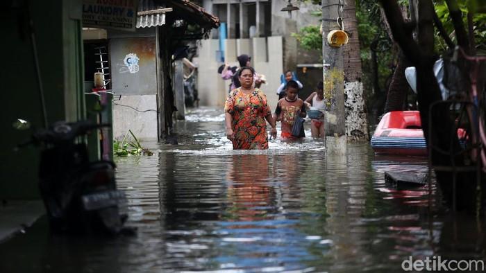 Warga melintasi banjir di RT 10 RW 05 Kelurahan Rawa Terate, Cakung, Jakarta Timur, Senin (24/2/2020). Banjir dikawasan ini sudah melanda sejak minggu 23 Februari hingga kini belum surut. Kemarin ketinggian air mencapai 2,5 m dan hari ini masih mencapai 60 cm. Menurut salah satu warga Sri Aminah hingga hari ini mereka belum mendapat bantuan dan mereka membutuhkan air bersih dan makanan. listrik dikawasan ini pun padam.