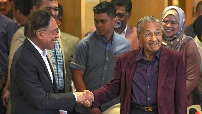 In this Feb. 22, 2020, photo, Malaysian Prime Minister Mahathir Mohamad shakes hand with successor Anwar Ibrahim in Putrajaya, Malaysia.  Political tension is building in Malaysia amid talks that Mahathir will pull his party out of the ruling alliance and team up with opposition parties to form a new government in a major political upheaval. It will thwart his named successor Anwar Ibrahim from taking over.(AP Photo/Vincent Thian)