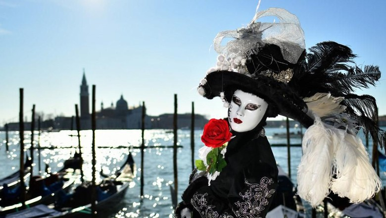 A reveller wearing a mask and a period costume takes part in the Venice Carnival on February 15, 2020. (Photo by Alberto PIZZOLI / AFP)