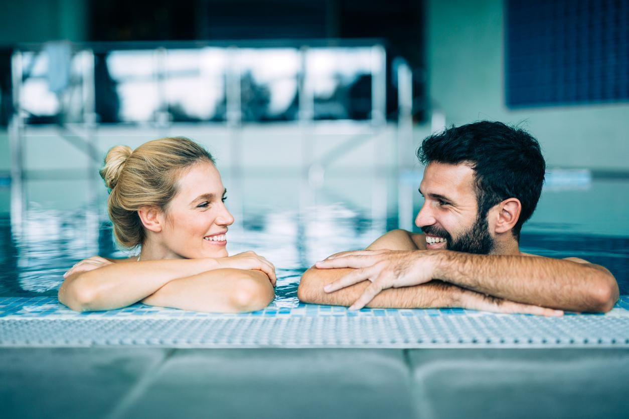 Happy attractive couple relaxing in spa swimming pool