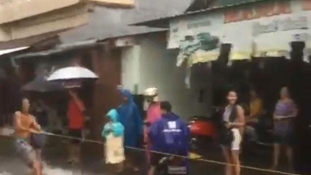 Pria berselancar di jalanan yang banjir
