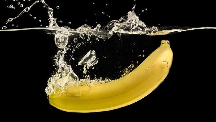 Ripe yellow banana splashing into clear water, black background
