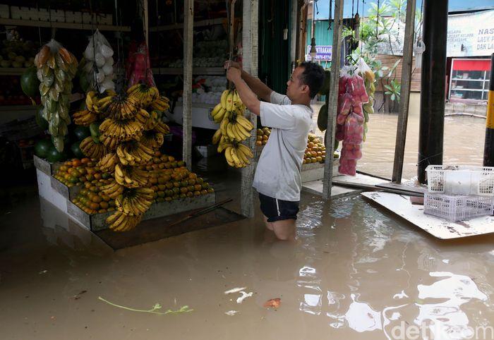Seorang pedagang tengah menata buah-buahan yang dijualnya di tengah banjir yang merendam kawasan kompleks Perumahan Rawalumbu, Narogong, Kota Bekasi, Selasa (25/2/2020).
