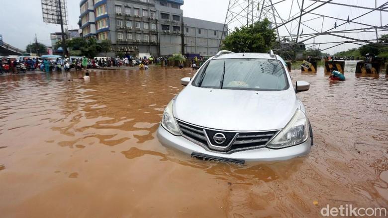Mobil mogok ditengah banjir di Bawah Kolong Tol JORR Kalimalang, Kota Bekasi, Jawa Barat, Selasa (25/2/2020). Jalan Drainase yang buruk dan hujan deras yang terus mengguyur wilayah Kota Bekasi dan sekitarnya, mengakibatkan banjir dan menyulitkan akses warga bekasi menuju Jakarta maupun sebaliknya .