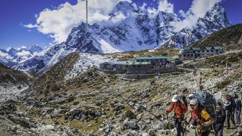 Lobuche, Nepal - 27th October 2014: Team of mountaineers trekking through the rocky moraine of the Khumbu valley along the Everest Base Camp trail from traditional teahouses overlooked by the vertiginous north faces of Taboche (6495m) and Cholatse (6440m) deep in the Himalaya mountain wilderness of the Sagarmatha National Park, a UNESCO World Heritage Site, Nepal. Composite panoramic image created from five contemporaneous sequential photographs.