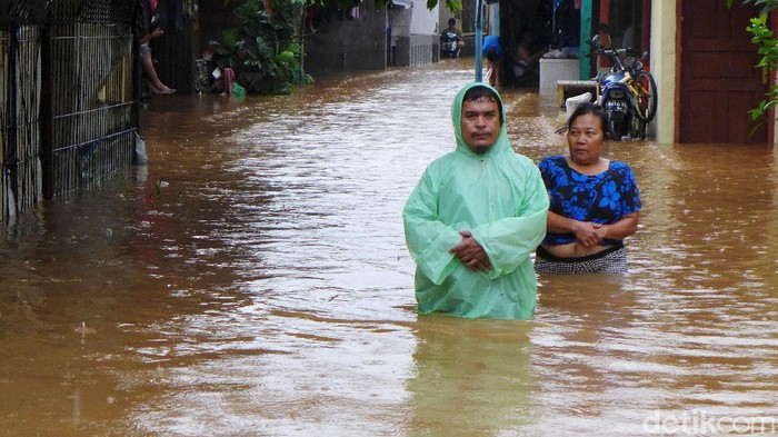 Sejumlah warga melintasi banjir di RT 2 RW 3 Rawadas, Pondok Kopi, Jakarta Timur, Selasa (25/2/2020). Banjir yang melanda kawasan ini mencapai 90 meter.