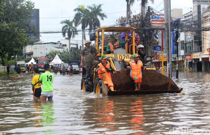 Banjir yang rendam jalan di Kedoya membuat warga kesulitan untuk beraktivitas. Alat berat hingga truk Satpol PP pun digunakan untuk bantu warga menerjang banjir