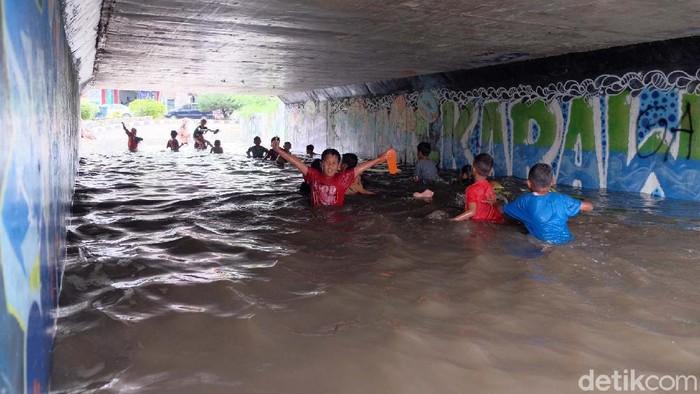 Banjir akibat hujan deras membuat Underpass Gonggo, Karawang, berubah seperti kolam renang. Anak-anak pun tampak asyik berenang di sana.