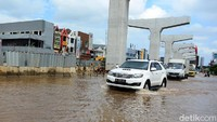 Seorang warga yang mengendarai mobil SUV Fortuner saat menerjang banjir di kawasan Ibu Kota Jakarta.