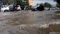 Sejumlah kendaraan roda dua dan roda empat menerobos genangan banjir di jalan yang berada di kawasan Bekasi.