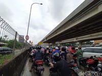 Pemotor antre masuk gerbang tol Becakayu untuk hindari banjir.