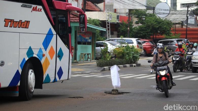 Di kawasan simpangan lima Jalan Wahid Hasyim Kebon Sirih, Jakarta Pusat, terdapat jalan berlubang yang cukup dalam.