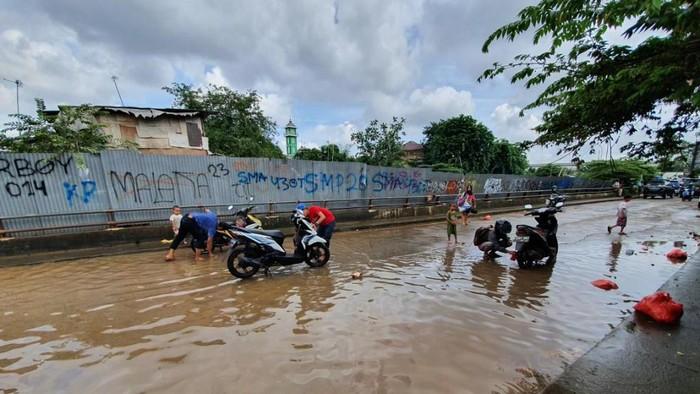 Warga mencuci motor di lokasi banjir di Kranji, Bekasi