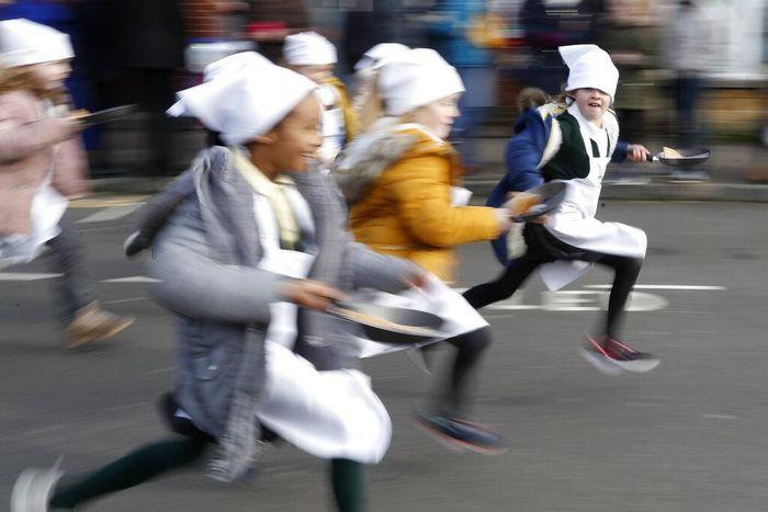 Anak-anak dan orang dewasa ikut serta dalam lomba balap lari sambil membawa pancake di Inggris. Diketahui perlombaan itu sudah ada sejak tahun 1445 lho.
