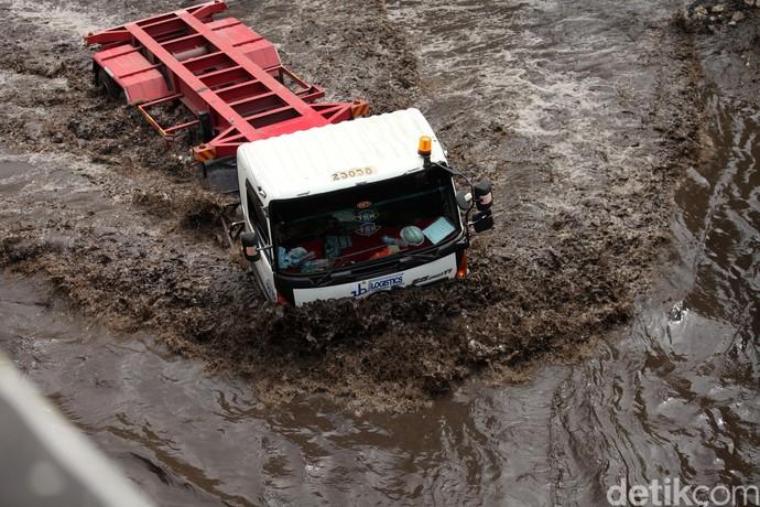 Begini aksi nekat para sopir truk saat melibas banjir di kawasan Cilincing, Jakarta Utara, Rabu (26/2). Banjir yang cukup tinggi tersebut tak menurunkan niat sopir untuk melintas.