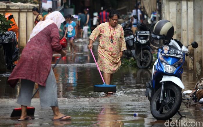 Banjir yang mulai surut di kawasan Cipinang Melayu, Jakarta Timur, dimanfaatkan warga untuk bersih-bersih rumah.
