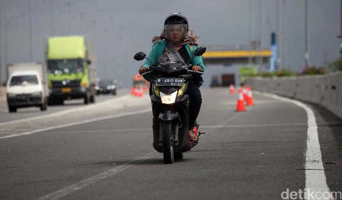 Pemotor diperbolehkan melintas di jalan tol lingkar luar timur, Cilincing, Jakarta Utara. Hal ini karena sebagian ruas jalan Cakung Cilincing Raya terendam banjir.