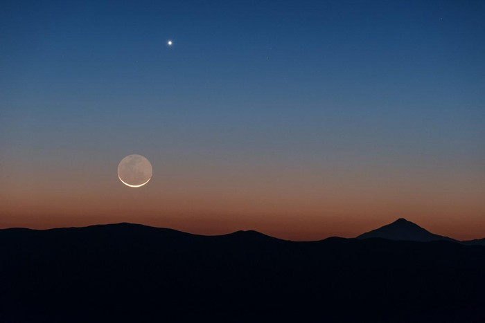 The perfect, clear viewing conditions above ESOs Paranal Observatory in Chile make for a fantastic opportunity to observe the wonders of the Universe. Sometimes, however, its nice to appreciate things closer to home, such as Earths trusty lunar companion, and one of its neighbouring planets, Venus, seen as the bright light to the Moons top-right. The rolling Chilean mountains provide a stunning silhouetted landscape beneath.
