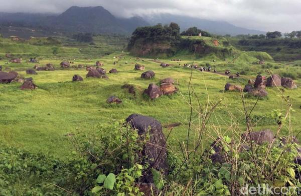 Tampak padang rumput hijau berhiaskan bebatuan dan bukit yang mengelilinginya.