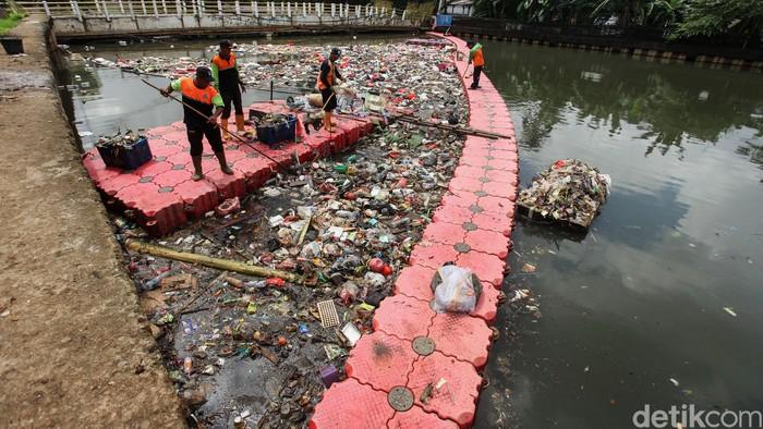Sejumlah petugas dari UPK Badan Air Jakarta tengah pembersihan sampah di Sungai Mookervart, Jakarta Barat, Rabu (26/2/2020). Hujan yang mengguyur Jakarta terus menerus membawa sampah hingga ke aliran sungai ini.