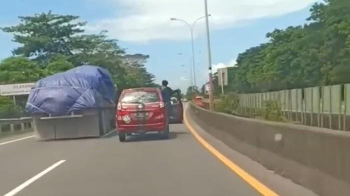 Pengemudi nyetir berdiri sambil buka pintu mobil di Makassar (Screenshot video viral)