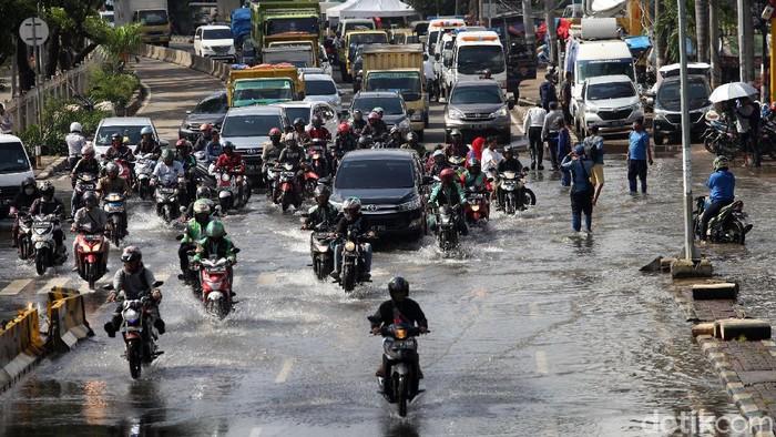 Sejumlah kendaraan melintas di perempatan Green Garden, Jakarta Barat, Rabu (26/2/2020). Hingga pagi ini terpantau jalanan masih tergenang.