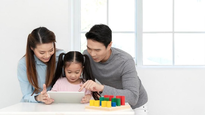 Happy young little asian cute girl watching or playing digital tablet, laptop or mobile with cheerful parents on desk in family time concept in white room with window. Preschool children learning.