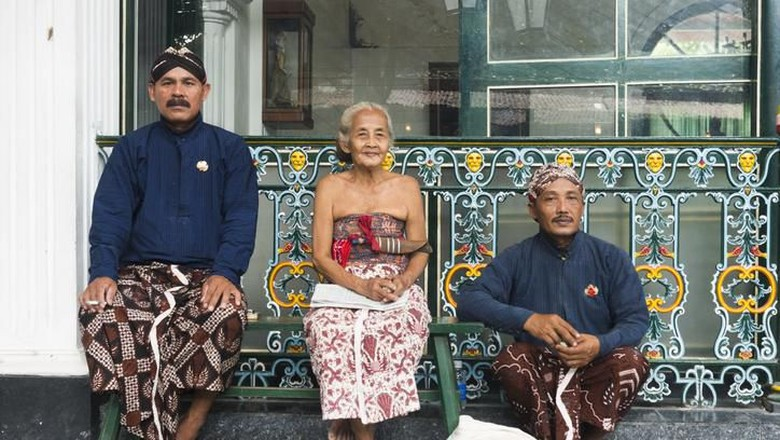 Yogyakarta, Indonesia - April 6, 2015: Three Javanese people wearing traditional clothing sit outside during a break while working at the Sultans Palace in Java, which is also called the Kraton. The two men wear head cloths and sarongs. The senior woman who sits in the middle wears a light colored sarong.