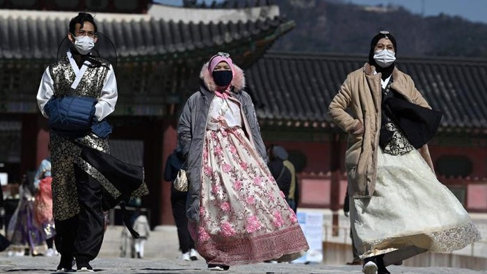 Visitors wearing face masks walk near the Gwanghwamun, the main gate of the 14th-century Gyeongbok Palace, and one of South Koreas well-known landmarks, in Seoul, South Korea, Saturday, Feb. 22, 2020. South Korea on Saturday reported a six-fold jump in viral infections in four days to 346, most of them linked to a church and a hospital in and around the fourth-largest city where schools were closed and worshipers and others told to avoid mass gatherings. (AP Photo/Lee Jin-man)
