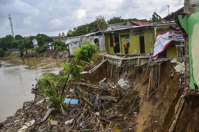 Warga mengamati rumahnya yang ambles akibat terkikis aliran kali daerah Teluk Pucung, Bekasi Utara, Jawa Barat,  Rabu (26/2/2020). Menurut warga, 34 rumah di bantaran aliran Kali Bekasi tersebut ambles sejak tahun 2017, tujuh rumah hilang dan 27 rusak berat. ANTARA FOTO/Fakhri Hermansyah/wsj.