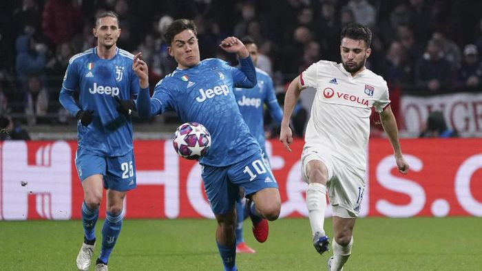 Juventus Paulo Dybala, center, and Lyons Leo Dubois, right, vie for the ball during a round of sixteen, first leg, soccer match between Lyon and Juventus at the at the Lyon Olympic Stadium in Decines, outside Lyon, France, Wednesday, Feb. 26, 2020. (AP Photo/Laurent Cipriani)