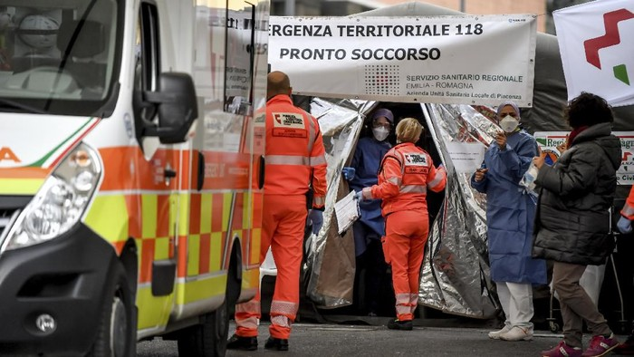 Paramedics stand next to a tent set up by the Italian Civil Protection outside the emergency ward of the Piacenza hospital, northern Italy, Thursday, Feb. 27, 2020. Italy is changing how it reports coronavirus cases and who will get tested in ways that could lower the countrys caseload even as an outbreak centered in northern Italy spreads in Europe. (Claudio Furlan/Lapresse via AP)